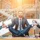 Manager meditiert auf Konferenztisch